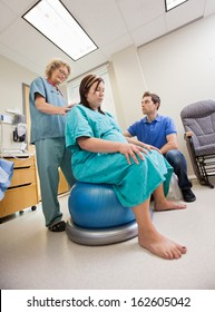 Mature female nurse assisting pregnant woman sitting on Pilate ball while man looking at her in hospital