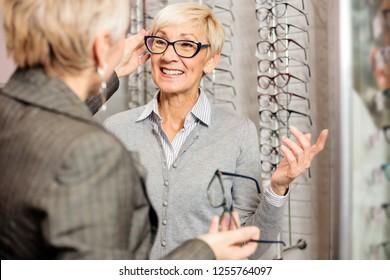 Mature female seller helping smiling senior woman to choose prescription glasses in optician store. Healthcare and medicine
