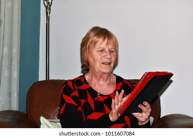 Mature female sitting in chair using hand held computer device, touching screen