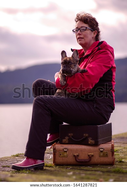 Mature female sitting on a wooden pier with her French bulldog puppy.