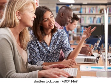 Mature Female Student With Tutor Learning Computer Skills