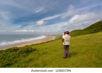 Mature female taking a photograph of a seascape on her mobile phone, Rhossili Bay, Gower, South West Wales, UK.