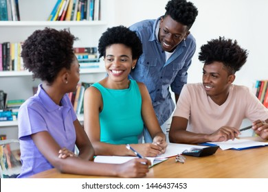 Mature female teacher with african american students at classroom of university