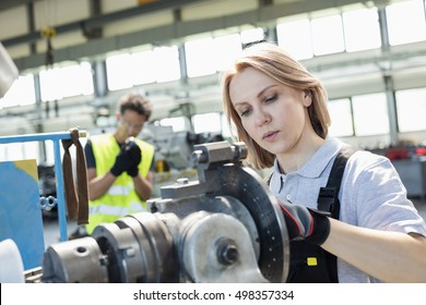 Mature female worker working on machinery with colleague in background at industry