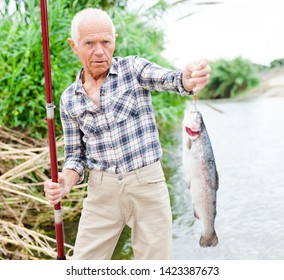 Mature fisherman with fishing rod in hand pulling fish caught from river