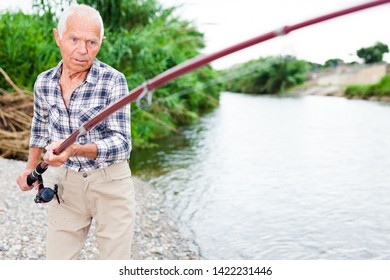 Mature fisherman standing on riverside and going to pull out catch fish