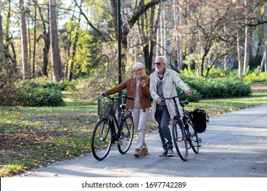 Mature fit couple pushing bicycles in public park talk and smile