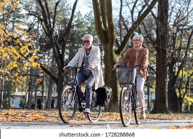 Mature fit couple ride in bicycles thru public park