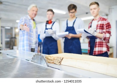 Mature foreman pointing at table saw and explaining students how to process wood, focus on metal workbench with wooden plank