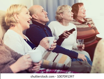 Mature friends are sitting on sofa and watching TV at home.