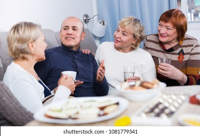 Mature friends are talking about life and drinking tea at home.
