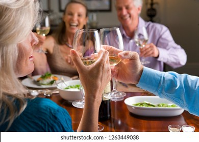 Mature friends toasting with wine enjoying meal in restaurant