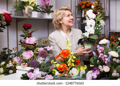 Mature glad female customer choosing flowers in floral department