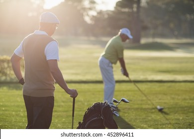 Mature golfer men standing on field during sunny day