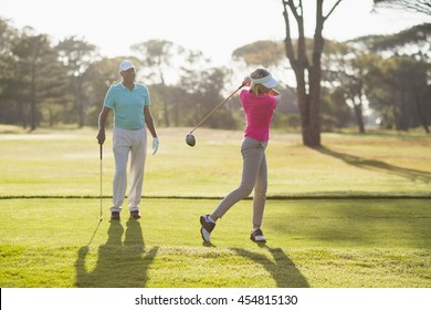 Mature golfer playing by man standing on field
