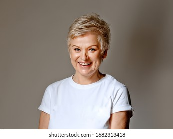 Mature grey haired  woman wearing white T-short posing. photo real woman without retouching.  Facial wrinkles and texture.