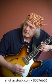 Mature guitarist with sunburst hollow body guitar and bandana