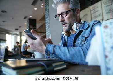Mature guy with eyeglasses connected on smartphone in bar
