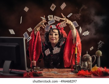 Mature Gypsy fortune teller is tossing up playing cards to predict future her online customer. Black-haired woman wears red-black blouse sitting at the desk with smoking candles and other occult items
