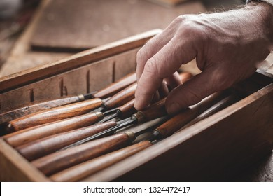 Mature hand reaching for a tool inside a wooden box