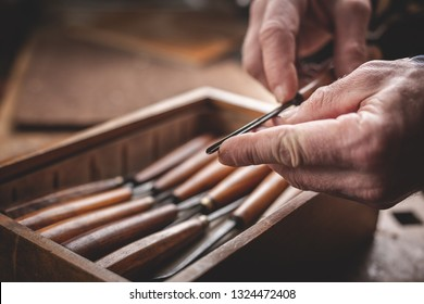 Mature hands holding a carving tool