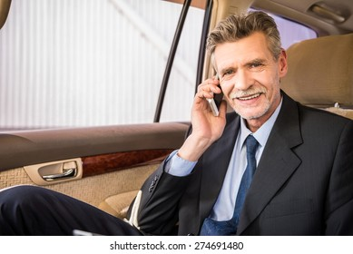 Mature handsome businessman sitting in his luxurious car and talking on the phone.