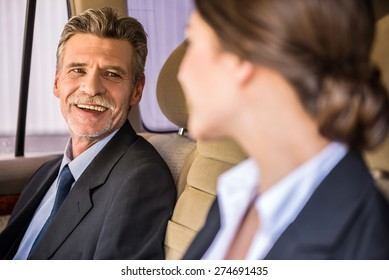 Mature handsome businessman in suit sitting in the car with his beautiful personal assistant and talking to her.