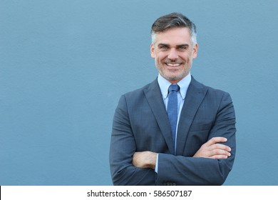 Mature handsome Caucasian businessman smiling with arms crossed