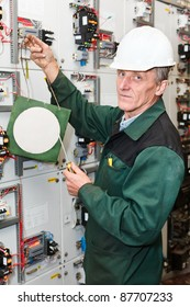 Mature handsome electrician working in hard hat with screwdriver and clear plate