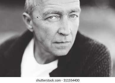 Mature handsome gray-haired man close up looking at the camera and posing