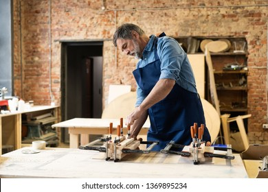 Mature handsome joiner work in carpentry. He is successful entrepreneur at his workplace