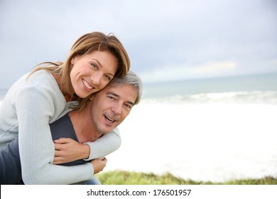Mature handsome man carrying woman on his back