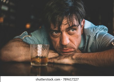 Mature handsome man enjoying whiskey in a bar. Toned picture