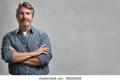 Mature handsome man portrait over gray wall background
