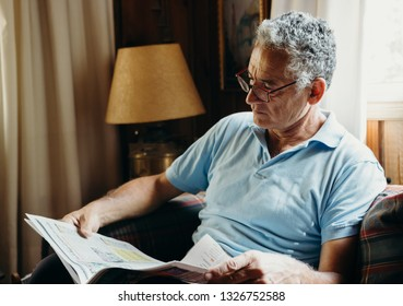 Mature handsome man reading the newspaper at home