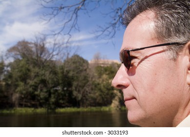 Mature, handsome, man smiling contentedly while enjoying the sunny weather and calm surrounding.