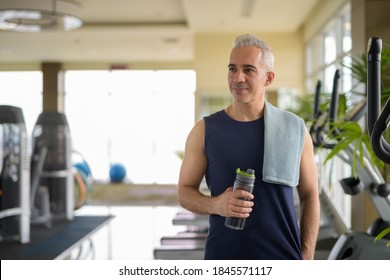 Mature handsome Persian man thinking while holding water bottle at the gym