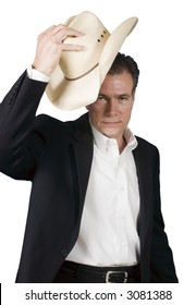 Mature, handsome, white male wearing a black suite and a white shirt holding a cowboy hat with one hand as tipping it in a polite greeting.
