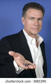 Mature, handsome, white male wearing a black suite and a white shirt holding a set of keys as if offering them to someone.