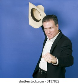 Mature, handsome, white male wearing a black suite and a white shirt holding a cowboy hat with one hand as if in celebration or exhilaration.