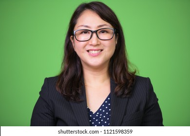 Mature happy beautiful Asian businesswoman smiling with eyeglasses against green background
