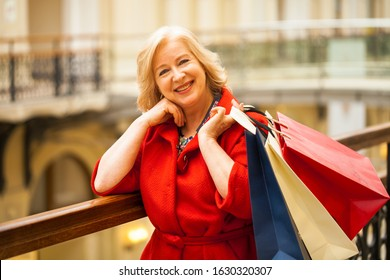 Mature happy blonde woman with shopping bags.