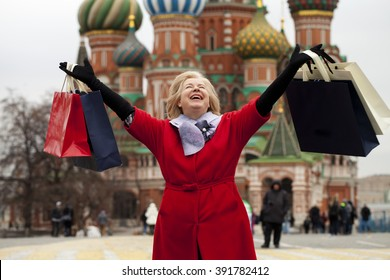 Mature happy blonde woman with shopping bags on Red Square in Moscow