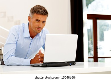 Mature happy businessman working with laptop