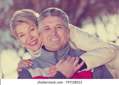 Mature happy couple walking along coastal park at sunny day. Focus on both persons