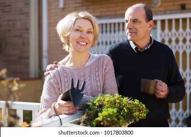 Mature happy female talking with male neighbor at balcon