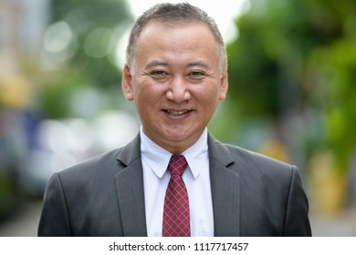 Mature happy Japanese businessman smiling in the streets outdoors