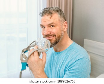 Mature happy man with chronic breathing issues considers using sitting on the bed in bedroom with CPAP machine. Healthcare, CPAP, snoring concept
