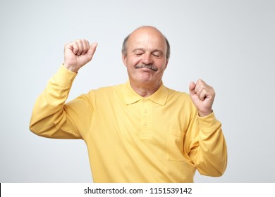 Mature happy man moving dancing over white background. He is enjoying every moment of his life