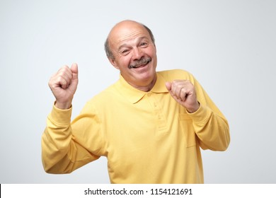 Mature happy man in yellow t-shirt moving dancing over white background. He is enjoying every moment of his life